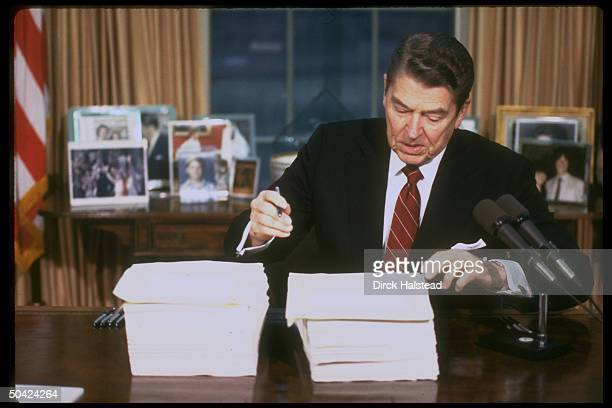 Pres Reagan poised w pen signing budget reconciliation bill in WH Oval Office