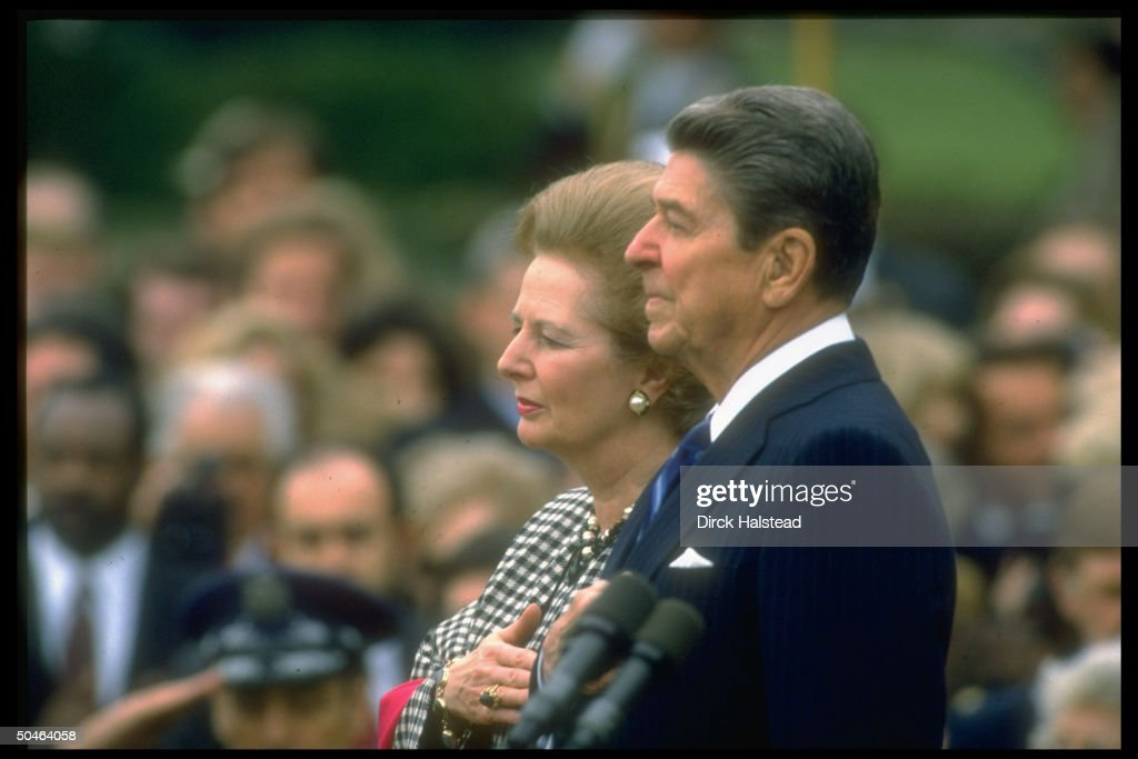 Pres. Reagan (R) w. British PM Thatcher, poised w. hands over hearts, during ceremony, outside, at WH.