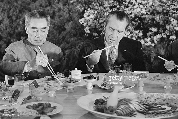 Pres Richard Nixon digs in with chopsticks as he sits beside Chinese Premier Chou Enlai during farewell banquet on the eve of Nixon's departure from...