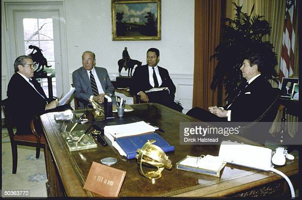 US Pres Ronald W Reagan seated at his desk in Oval Office discussing the upcoming summit with Soviet leader Mikhail S Gorbachev with WH Chief of...