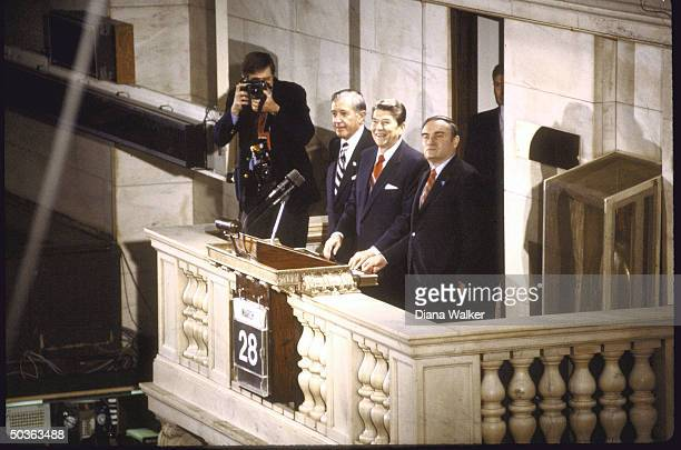 US Pres Ronald W Reagan standing on indoor balcony overlooking crowd with WH Chief of Staff Donald T Regan and Chrmn New York Stock Exchange John J...