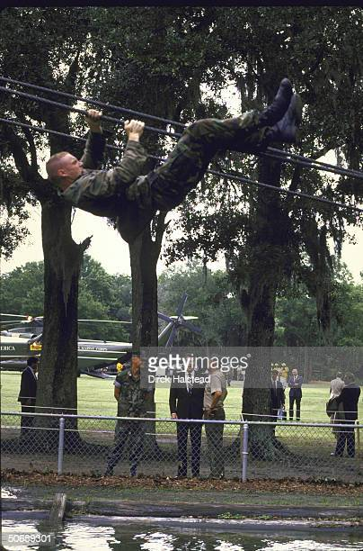 US Pres Ronald W Reagan watches Marines physical training exercise with secret servicemen lurking in trees