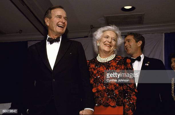 Pres. & signature pearls sporting Barbara Bush having high old time at TX-style black tie & boots inaugural ball, w. Their son George .