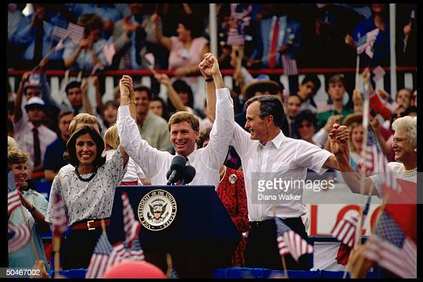 GOP pres team cands VP Mrs Bush Dan Mrs Quayle raising linked hands framed by supporters at Riverwalk campaign rally