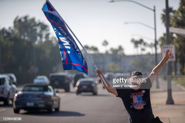 Pres. Trump supporter Steve Martin, of Westminster, joins fellow supporters as he dances and cheers on passing motorists in front of the Republican...