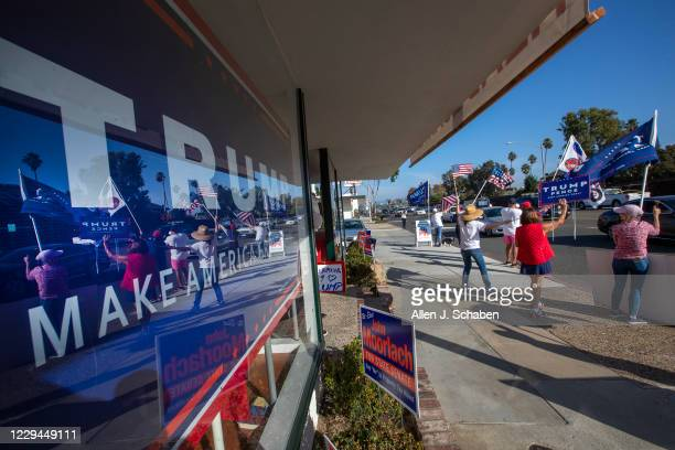 Pres. Trump supporters cheer on passing motorists in front of the Republican Party headquarters on election day Tuesday, Nov. 3, 2020 in Newport...
