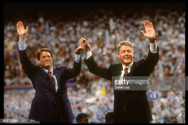 Pres VP nominee Bill Clinton Al Gore raising clasped hands victoriously waving w their free arms to crowd on floor of Democratic Convention at...