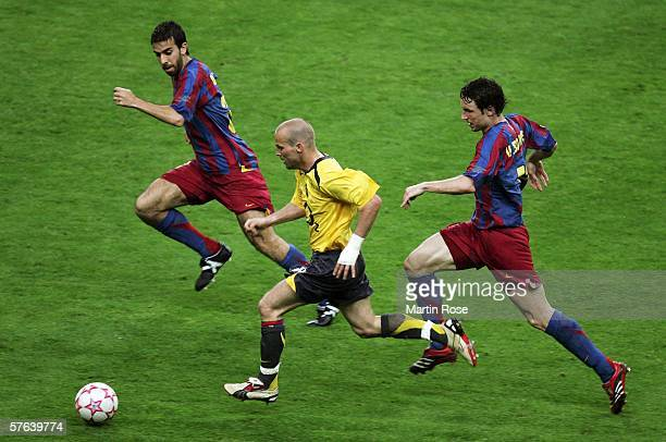 Presas Oleguer and Mark Van Bommel of Barcelona surround Fredrik Ljungberg of Arsenal during the UEFA Champions League Final between Arsenal and...