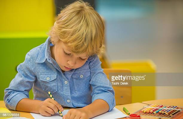 Prescholl Boy Sitting At Table And Draws