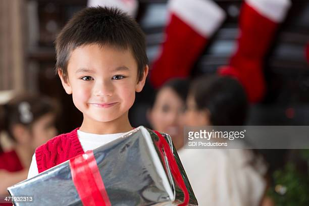 Preschool age Asian boy opening Christmas presents with family