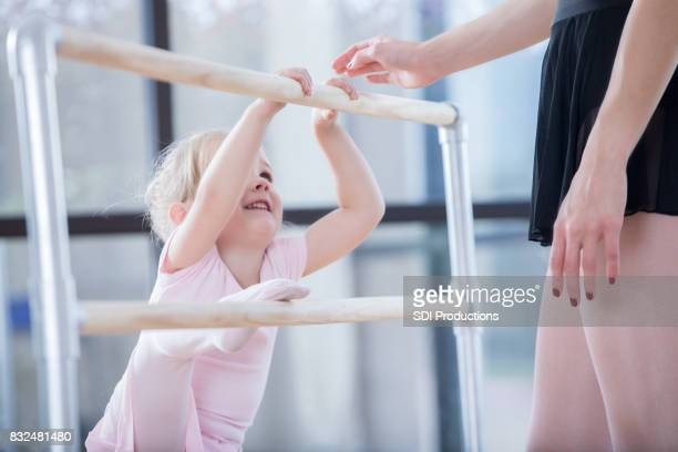 Preschool age ballerina receives instruction at ballet barre