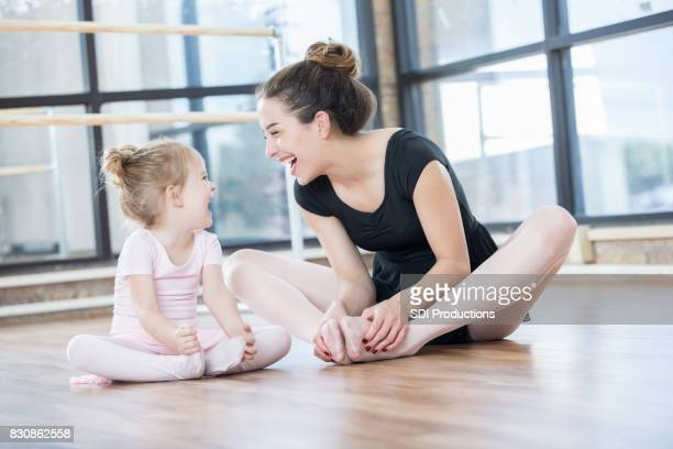 Preschool age ballet student and instructor laugh during floor stretches