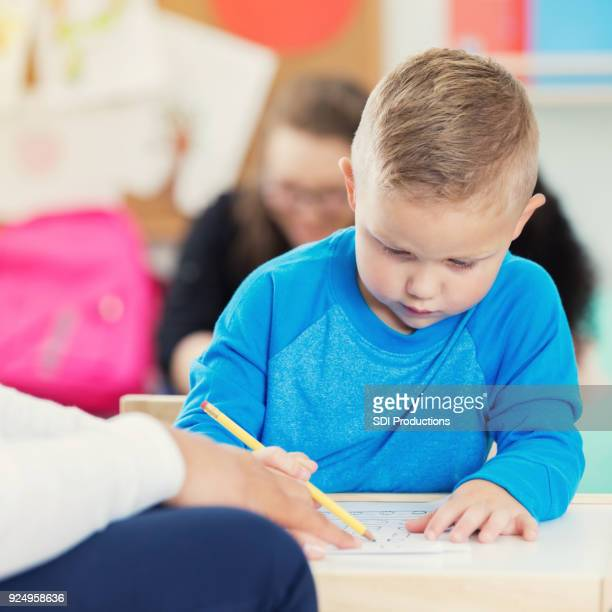 Preschool age boy concentrates on writing assignment