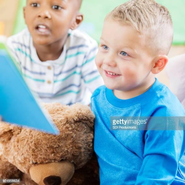 Preschool age boy listens with teddybear and classmate during storytime