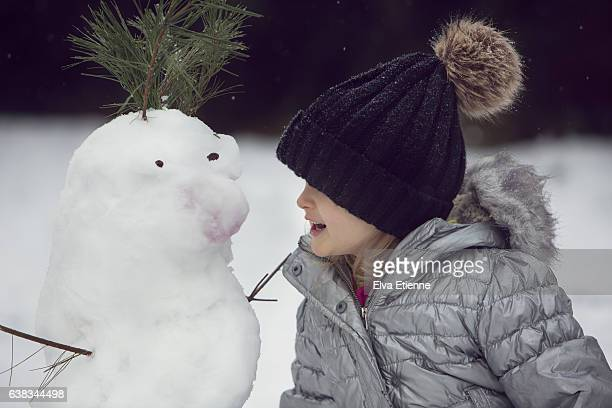 Preschool age child talking to snowman