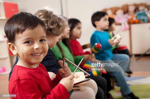 preschool age children in music class - triangle percussion instrument stock photos and pictures