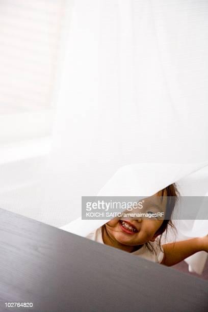 Preschool age girl playing hide and seek