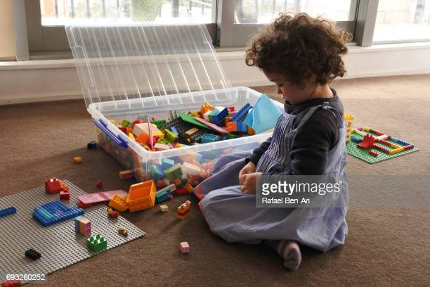 preschool age girl plays with building blocks - rafael ben ari stockfoto's en -beelden
