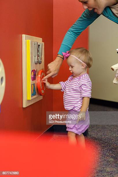 preschool age girl plays with interactive learning toy at library - baby pointing stock photos and pictures
