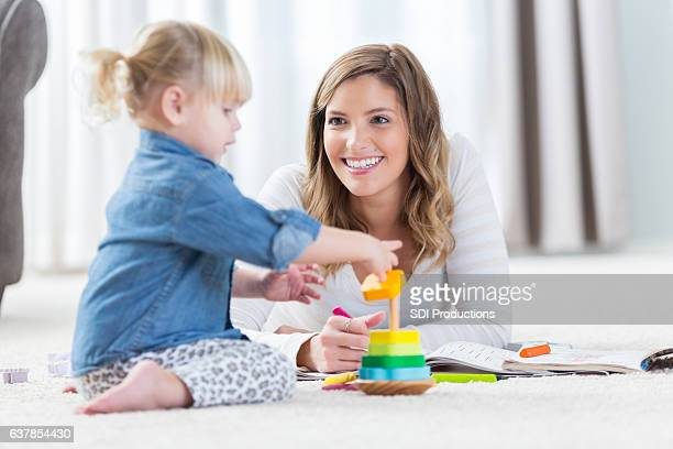 Preschool age girl plays with stackable toy with her mom