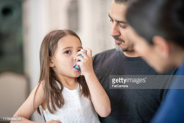 preschool age girl with asthma learns to use an inhaler - asthma stock pictures, royalty-free photos & images
