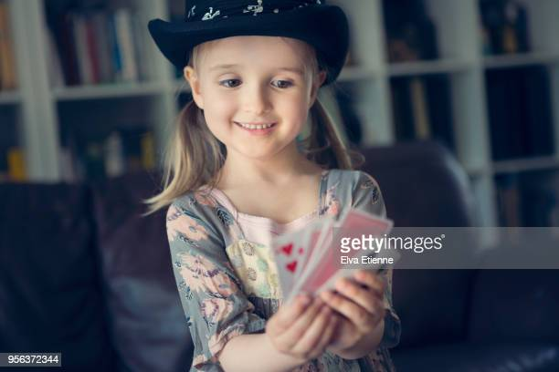pre-school aged child performing a magic trick with playing cards - zaubertrick stock-fotos und bilder