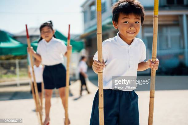Preschool aged children learning to use stilts as part of their physical education
