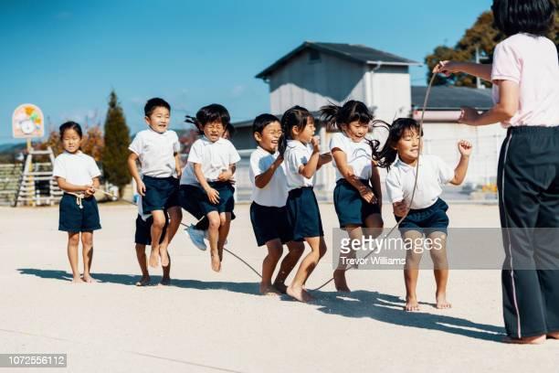 preschool aged children practicing with a jump rope with their teacher - sports uniform stockfoto's en -beelden