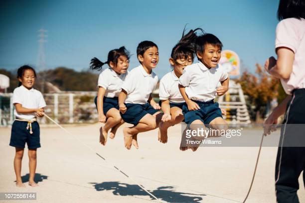 preschool aged children practicing with a jump rope with their teacher - only japanese stock pictures, royalty-free photos & images