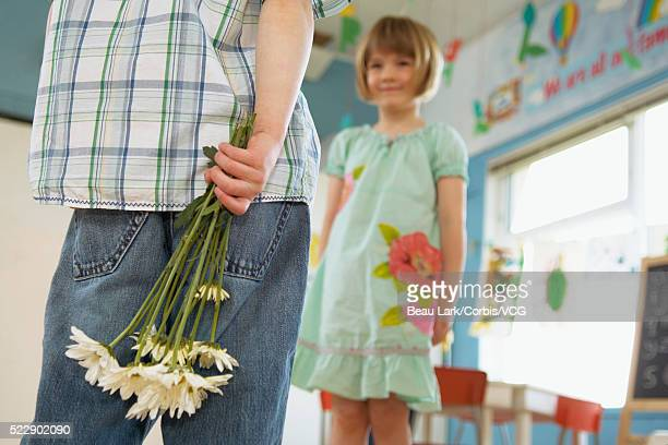 Preschool boy bringing flowers to girl