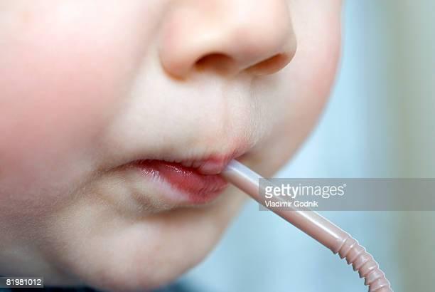 A preschool boy drinking from a straw