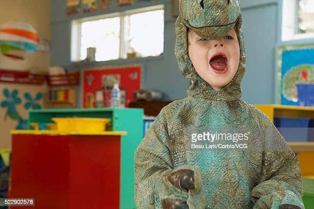 Preschool boy in dinosaur costume