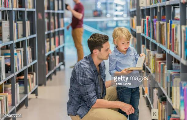 preschool boy with his father in public library - human relationship stock pictures, royalty-free photos & images
