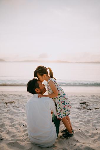 Preschool child kissing father on beach at sunset, Okinawa, Japan - gettyimageskorea