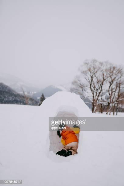Preschool child making igloo on snowy field in mountains