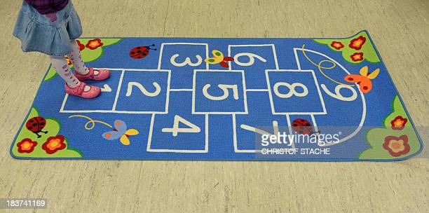 A preschool child stands on a carpet to play hopscotch at a Kindergarten a preschool institution for children between 3 and 6 years in Eichenau near...