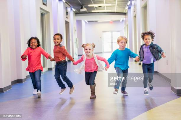 preschool children holding hands running down hallway - children only stock pictures, royalty-free photos & images
