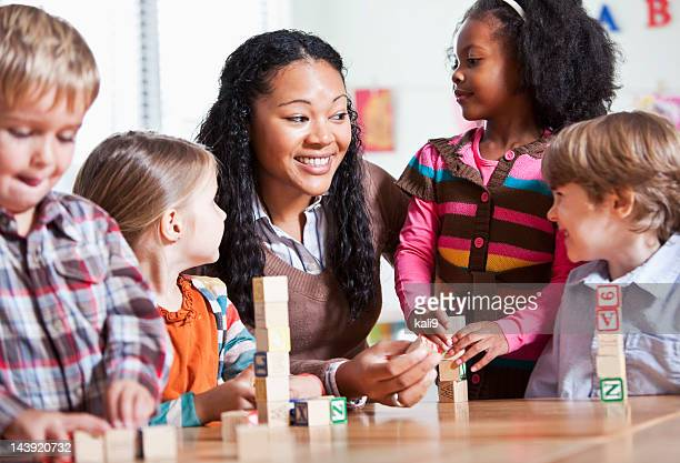 preschool children in classroom with teacher - nursery school child stock pictures, royalty-free photos & images