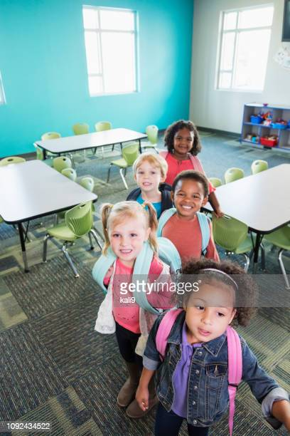 preschool children lined up in classroom with backpacks - preschool student stock pictures, royalty-free photos & images