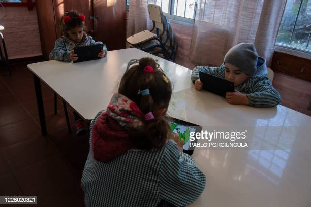 "Pre-school children use their ""Ceibalita tablets"" during a class in a public school in Montevideo, amid the COVID-19 novel coronavirus pandemic, on..."