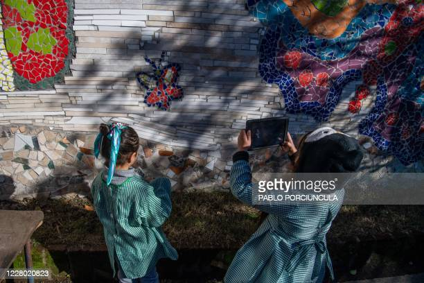 "Pre-school children use their ""Ceibalita tablets"" to take pictures during a class in a public school in Montevideo, amid the COVID-19 novel..."