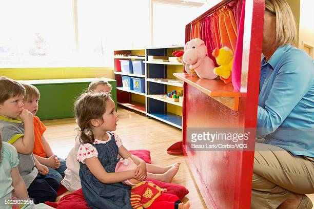 preschool children watching a puppet show - puppet show stock photos and pictures