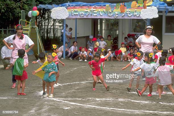 Preschool children wear capes and dance for a sports day at their daycare center in Urayasu Tokyo Japan