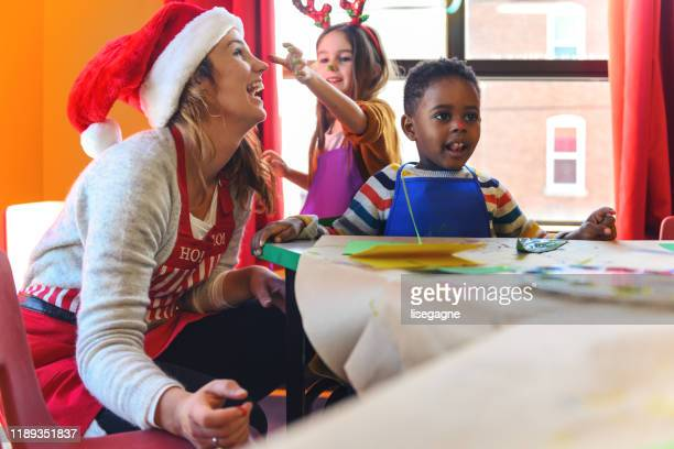 preschool christmas activities - 4 girls finger painting stock pictures, royalty-free photos & images