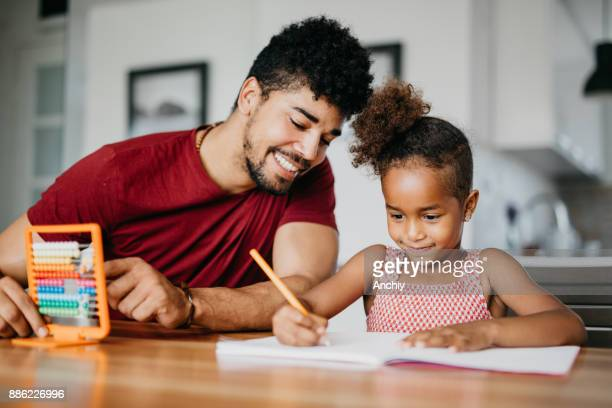 Preschool girl and father are calculating on abacus at home