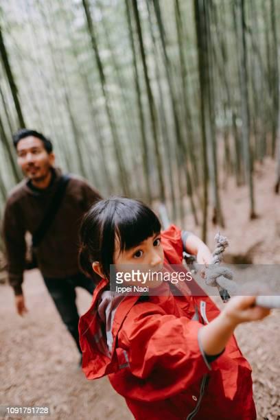 Preschool girl climbing mountain with bamboo forest