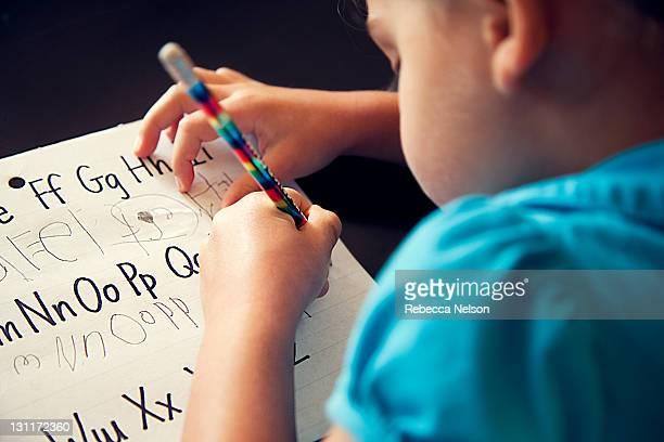 preschool girl copying her letters - 左利き ストックフォトと画像