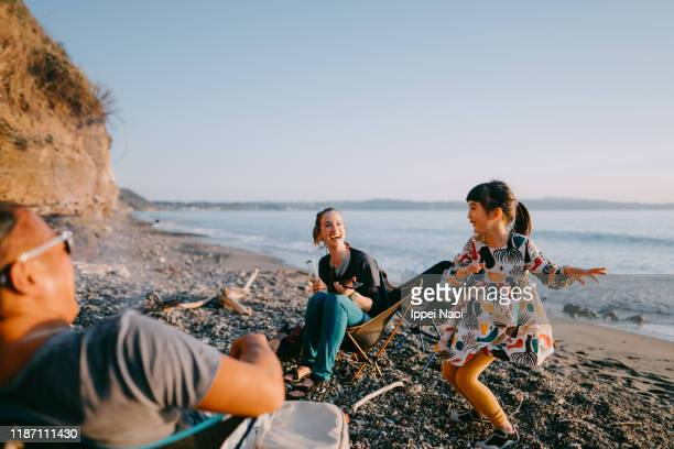 preschool girl dancing for her family at beach camping site - alternative pose stock pictures, royalty-free photos & images