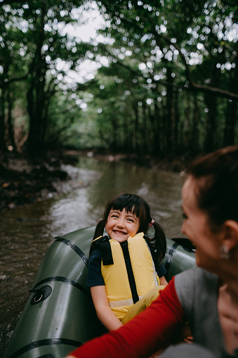 Preschool girl having fun with raft and smiling at camera in mangrove swamp, Japan - gettyimageskorea