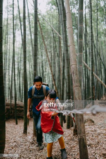 Preschool girl hiking mountain with bamboo forest